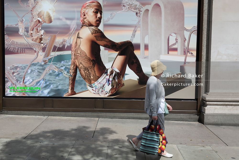 An elderly lady walks past a sexy young male in an advert for mens' underwear outside the London location of the Selfridges Department store on Oxford Street, on 2nd July 2019, in London, England.