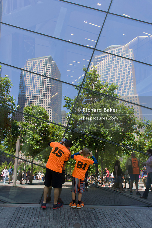 Visitors wearing identical shirts peer into plate glass window at the 9/11 Memorial in New York, killed at the locations of terrorist attacks on September 11th 2001. The National September 11 Memorial is a tribute of remembrance and honor to the nearly 3,000 people killed in the terror attacks of September 11, 2001 at the World Trade Center site, near Shanksville, Pa., and at the Pentagon, as well as the six people killed in the World Trade Center bombing in February 1993.
