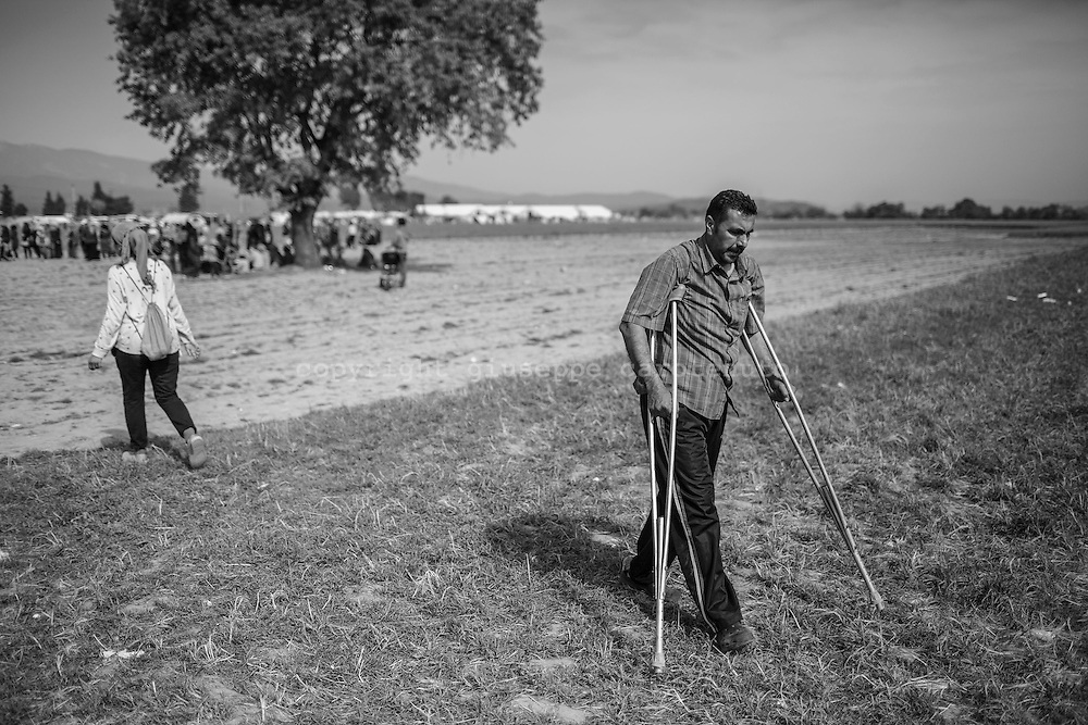 19 April 2016, Greece, Idomeni - A refugee walks on crutches in the refugees camp of Idomeni.