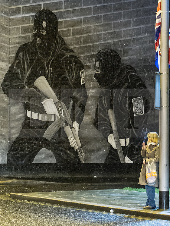 © Licensed to London News Pictures . 10/01/2013 . Belfast , UK . A woman waits at a bus stop below a mural painted on a wall in East Belfast . On 3rd December 2012 , councillors voted to limit the number of days the Union flag would be flown above Belfast City Hall , sparking weeks of violence . Photo credit : Joel Goodman/LNP.