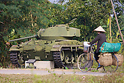 Cyclist passing a French Bazeille tank destroyed by Viet Minh forces.