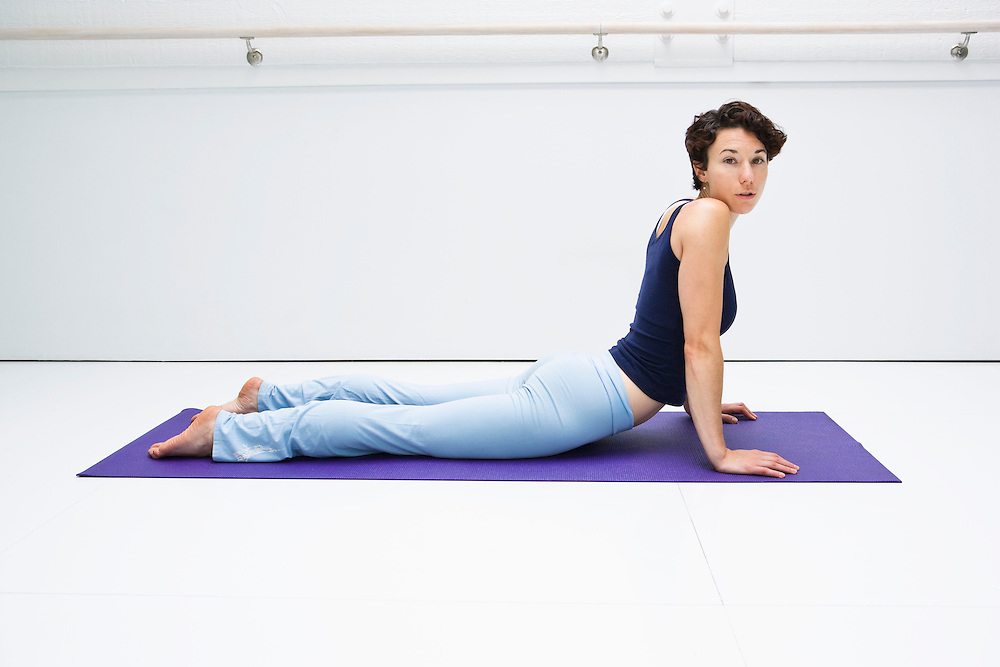 Young woman doing the Cobra pose in a white room on a yoga mat while looking to the camera.