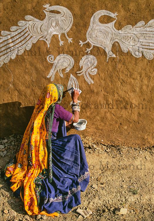 Inde. Rajasthan. Village dans les environs de Tonk. Une femme peint le mur de sa maison (Thapa) pour la fête de nouvel année (Diwali). // India. Rajasthan. Village near Tonk. Woman painting house wall (Thapa) for new year festival (Diwali).