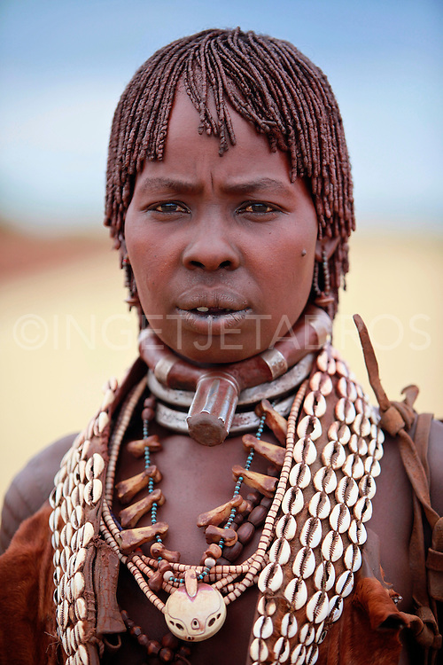 Hamar women are known for practice of body adornment and roll their locks with fat and red ochre (assile) and than twist them into crimson-colored dreads called Goscha, a style thet men find attractive..Dimeka, Omo Valley, Ethiopia, 2010
