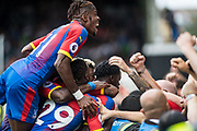 Jeffrey Schlupp (15) of Crystal Palace, Wilfried Zaha (11) of Crystal Palace, celebrates after scoring goal during the Premier League match between Fulham and Crystal Palace at Craven Cottage, London, England on 11 August 2018.