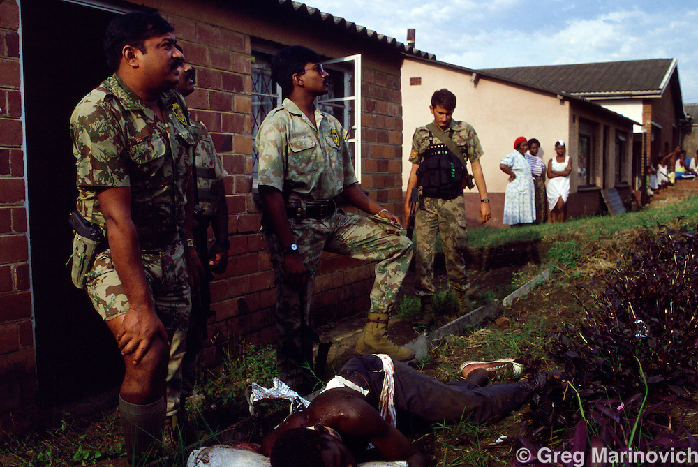 KwaMashu township, KwaZulu Natal, Durban, South Africa. Police stand above man shot in clashes between African National Congress and Inkatha Freedom Party supporters, 1994.