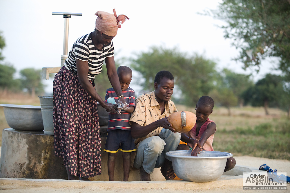 Family members wash their hands near a water pump outside their village.