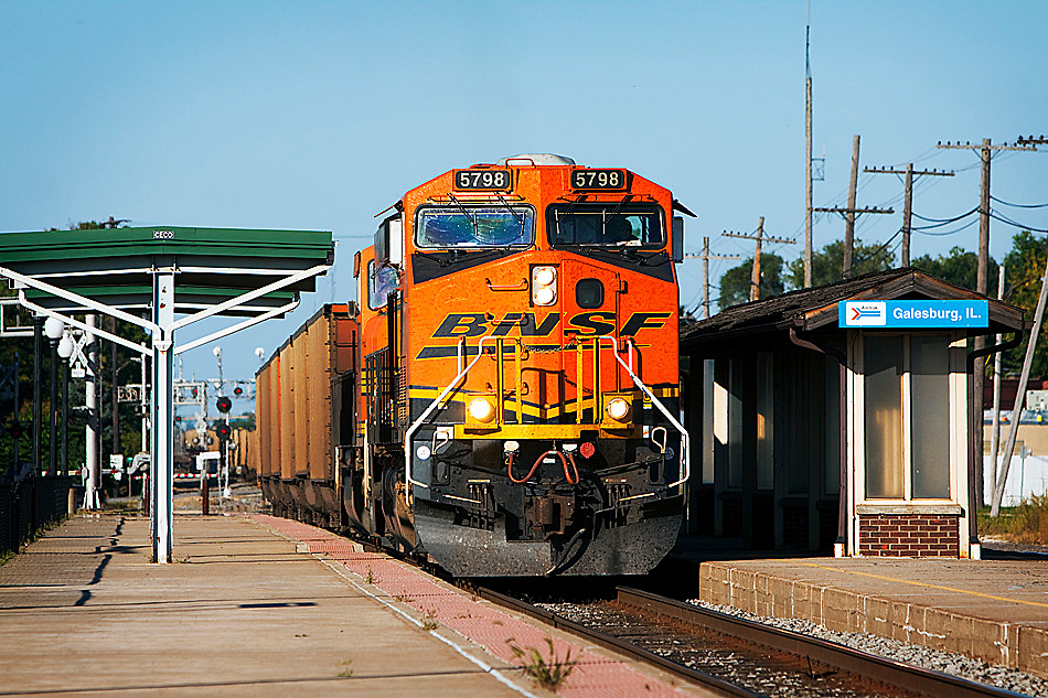 An empty BNSF coal train rolls slowly through the Amtrak depot in Galesburg, IL.