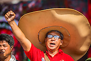 20 NOVEMBER 2013 - BANGKOK, THAILAND:  A Red Shirt supporter wearing a giant cowboy hat raises a clenched fist in support of the government Wednesday. Thousands of Red Shirts, supporters of the Pheu Thai ruling party in Thailand, gathered in Rajamangala Stadium in suburban Bangkok to listen to the Thai Constitutional Court deliver its verdict against the government. The court ruled that the recent efforts by the government to pass a blanket amnesty bill violated the Thai Constitution but the court did not order the party to disband or the dissolution of the government, which had been widely feared.    PHOTO BY JACK KURTZ