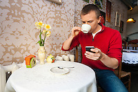 Man having coffee while reading text message on cell phone at cafe