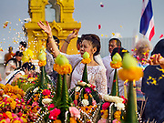 15 NOVEMBER 2018 - BANGKOK, THAILAND:  A woman makes merit by throwing an offering of flower petals during the red cloth ceremony at Wat Saket, also called the Golden Mount. Wat Saket is on a man-made hill in the historic section of Bangkok. The temple has golden spire that is 260 feet high, which was the highest point in Bangkok for more than 100 years. The temple construction began in the 1800s during the reign of King Rama III and was completed in the reign of King Rama IV. A  red cloth (reminiscent of a monk's robe) is placed around the chedi at the top of  Golden Mount during the weeks leading up to the Thai holy day of Loy Krathong, which is November 22 this year.      PHOTO BY JACK KURTZ