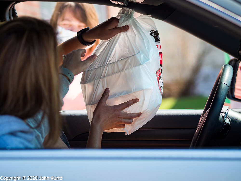 """26 APRIL 2020 - JEWELL, IOWA: A motorist in Jewell brings a sack of """"grab and go"""" roast pork dinners into her car in Jewell Sunday. Jewell, a small community in central Iowa, became a food desert when the only grocery store in town closed in 2019. It served four communities within a 20 mile radius of Jewell. Some of the town's residents are trying to reopen the store, they are selling shares to form a co-op, and they hold regular fund raisers. Sunday, they served 550 """"grab and go"""" pork roast dinners. They charged a free will donation for the dinners. Despite the state wide restriction on large gatherings because of the COVID-19 pandemic, the event drew hundreds of people, who stayed in their cars while volunteers wearing masks collected money and brought food out to them. Organizers say they've raised about $180,000 of their $225,000 goal and they hope to open the new grocery store before summer.           PHOTO BY JACK KURTZ"""