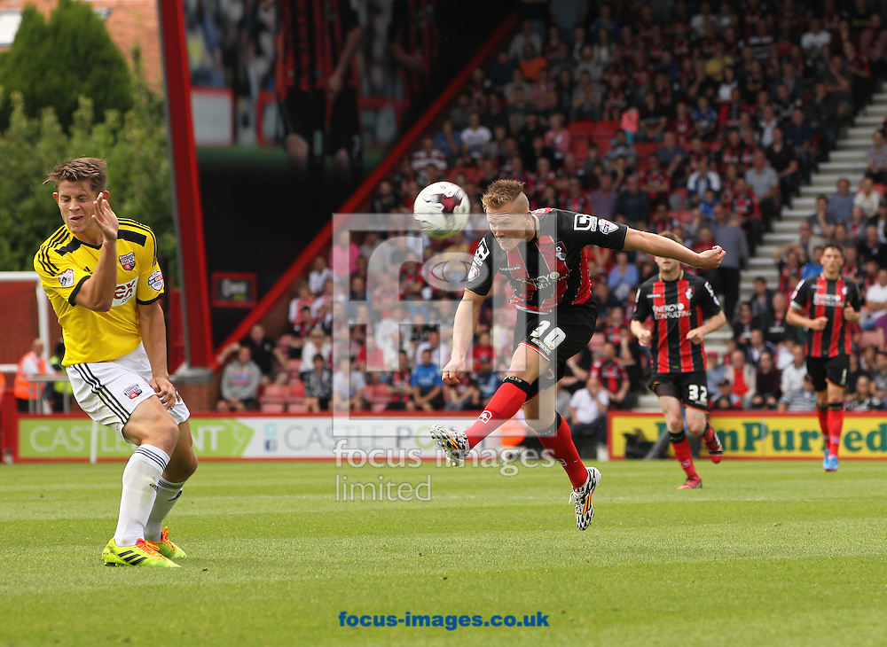Matt Ritchie (right) of Bournemouth takes a shot but it is blocked by James Tarkowski (left) of Brentford during the Sky Bet Championship match at the Goldsands Stadium, Bournemouth<br /> Picture by Tom Smith/Focus Images Ltd 07545141164<br /> 16/08/2014