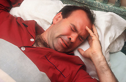 Man lying in bed with pained expression,