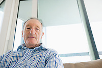 Portrait of senior man relaxing in living room