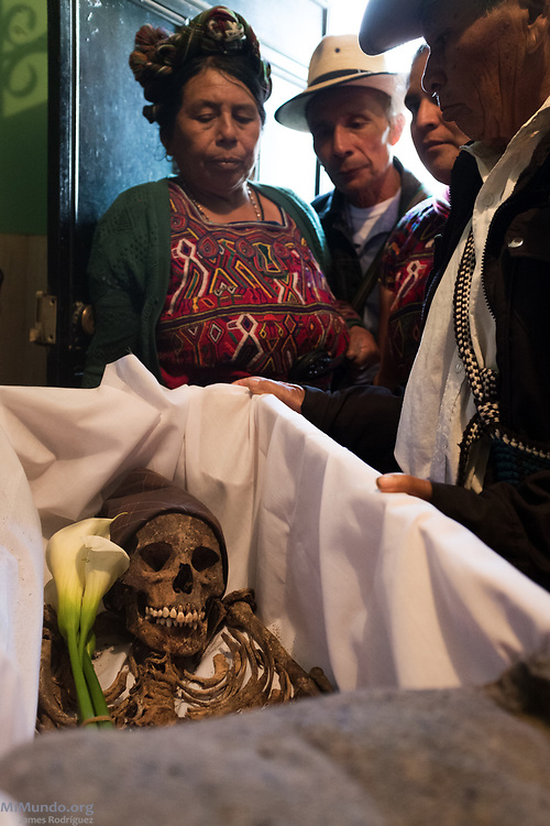 Family members watch as the remains of Ignacia Calel Vargas are arranged in a coffin. Ixil Mayan residents of Nebaj gather as the human remains of 36 war victims, including Solis de Leon's, are returned to their surviving family members for a proper burial. Most of the victims, exhumed from mass graves in Xe'xuxcap, near Acul, starved in the mountainside while fleeing State-led repression in 1982. Most of the remains, exhumed by members of the Forensic Anthropology Foundation of Guatemala (FAFG) in 2013, were identified using DNA analysis and buried 35 years after their death. Nebaj, Quiché, Guatemala. February 2, 2017.