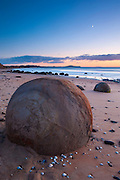Dozens of large, almost perfectly spherical rocks known as the Moeraki Boulders line Koekohe Beach in New Zealand. About two-thirds of the rocks range in size from 1.5 to 2.2 metres (4.6 to 6.7 ft).