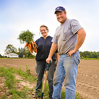 Ontario farmers Jessie and Ben Sosnicki proudly hold a bunch of their freshly harvested, organic carrots on their farm near Waterford, Ontario.