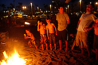 21 June 2008:  Family gathers around a wood burning fire pit during beach bonfire at tower 9 in Huntington Beach, CA.