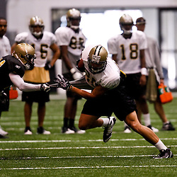 July 31, 2010; Metairie, LA, USA; New Orleans Saints tight end Jimmy Graham (80) is grabbed by cornerback Leigh Torrence (24) during a training camp practice at the New Orleans Saints indoor practice facility. Mandatory Credit: Derick E. Hingle