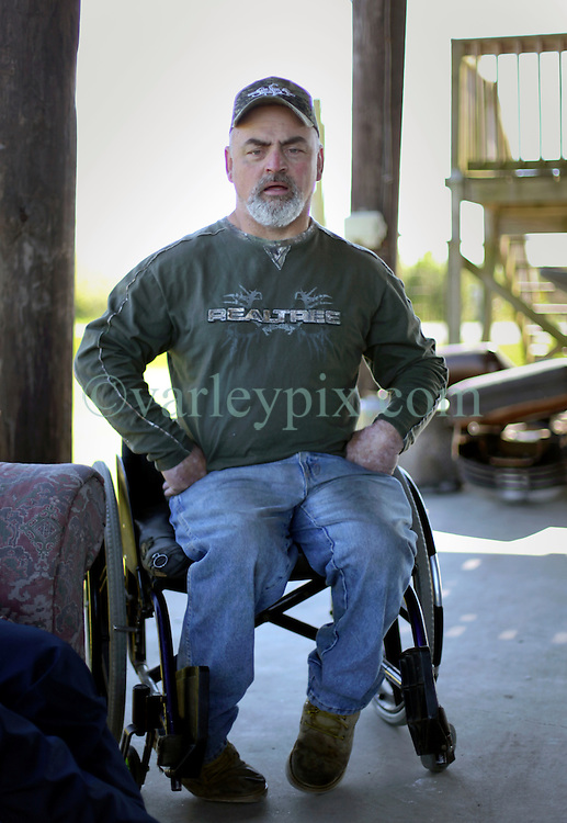 04 March 2016. Isle de Jean Charles, Louisiana.<br /> Vanishing land. First climate refugees in the USA. Isle de Jean Charles Band of Biloxi-Chitimacha Indians.<br /> Chris Brunet of the tribal council at home in his wheelchair. The tribe has recently been awarded $52 million to resettle on higher ground as more and more of their land is consumed by erosion from the Gulf of Mexico.<br /> Photo©; Charlie Varley/varleypix.com