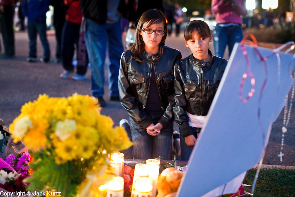tucsonshooting - 09 JANUARY 2011 - TUCSON, AZ: Juni Escamillas (CQ) LEFT, 11, and her sister, Yareli Escamillas pray at a memorial for Gabrielle Giffords at University Medical Center in Tucson Sunday night. Congresswoman Gabrielle Giffords, US Federal Judge John Roll and several other people were shot by a lone gunman in a mass shooting Saturday.     ARIZONA REPUBLIC PHOTO BY JACK KURTZ