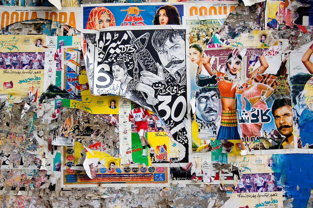 LAHORE, PAKISTAN - MAY 11: Weather beaten posters layer the wall of a building in the film-poster painting district on Friday, May 11, 2007, in Lahore, Pakistan. Billboard painters have had to cut their prices in half due to few Lollywood productions and the use of soft-porn posters to entice patrons. As thawing relations between Pakistan and India lead them closer to regional stability, Pakistan's film industry takes another hit as Bollywood films dominate an already floundering institution, as the Pakistani government eases a 43-year-old ban on screening Indian films and audiences are drawn to their neighbours silver-screen theatrics. Once a thriving film industry in the chaotic and colourful city of Lahore, Pakistan's answer to Bollywood - Lollywood - is now a shadow of its former self. Two decades ago 11 studios averaged a collective 100+ films per year as cinemagoers filled more than 1000 theatres across the country. Today, only one functioning studio struggles to produce a single film for the country's 200 decaying theatres. (Photo by Warrick Page)