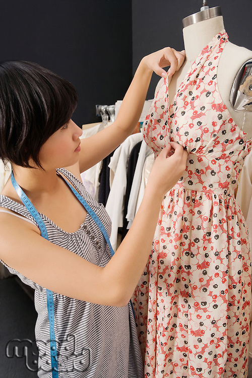 Woman adjusting fabric on dummy