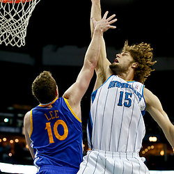 Mar 18, 2013; New Orleans, LA, USA; New Orleans Hornets center Robin Lopez (15) shoots over Golden State Warriors power forward David Lee (10) during the second quarter a game at the New Orleans Arena Mandatory Credit: Derick E. Hingle-USA TODAY Sports