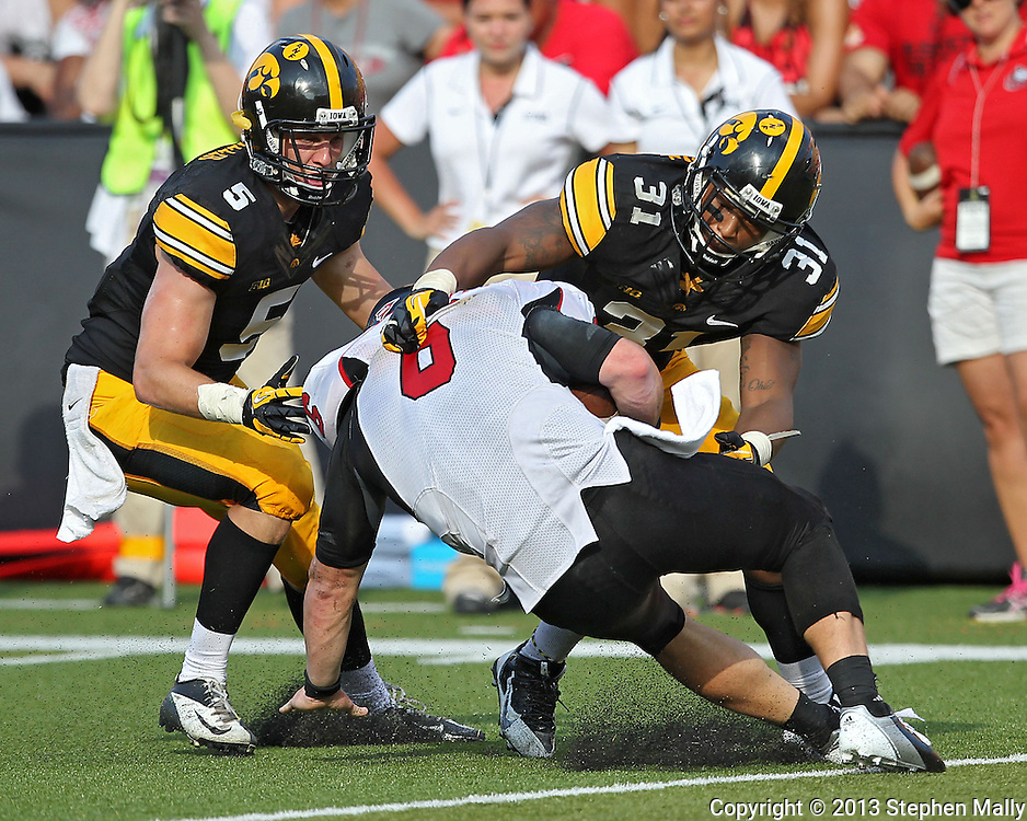 August 31 2013: Northern Illinois Huskies quarterback Jordan Lynch (6) is hit by Iowa Hawkeyes defensive back Tanner Miller (5) and Iowa Hawkeyes linebacker Anthony Hitchens (31) during the second half of the NCAA football game between the Northern Illinois Huskies and the Iowa Hawkeyes at Kinnick Stadium in Iowa City, Iowa on August 31, 2013. Northern Illinois defeated Iowa 30-27.