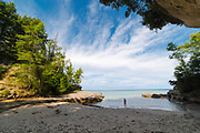 """A young girl walks in the sand. Image from the area known as """"The Cove,"""" Pictured Rocks National Lakeshore, Michigan, USA."""