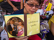 01 AUGUST 2013 - BANGKOK, THAILAND: A woman with up a picture of Bhumibol Adulyadej, the King of Thailand, and his wife, Queen Sirikit, in front of Siriraj Hospital, before the King left the hospital Thursday. The King, 85, was discharged from Bangkok's Siriraj Hospital, where he has lived since September 2009. He traveled to his residence in the seaside town of Hua Hin, about two hours drive south of Bangkok, with his wife, 80-year-old Queen Sirikit, who has also been treated in the hospital for a year.        PHOTO BY JACK KURTZ