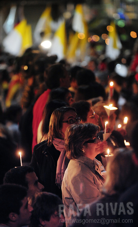 People light candles as they wait for Pope Benedict XVI to arrive, on november 6, 2010, in Barcelona. Benedict will visit Barcelona on November 7 where he will be consecrating Barcelona famous temple, the Sagarada Famila church.   PHOTO/Rafa Rivas