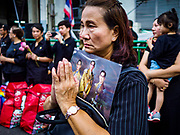 13 OCTOBER - BANGKOK, THAILAND: A woman holding a portrait of the late King prays on the first anniversary of the death of Bhumibol Adulyadej, the Late King of Thailand. About 199 monks from 14 Buddhist temples in Bangkok participated in the mass merit making at Siriraj Hospital to mark the anniversary of the revered King's death. He will be cremated on 26 October 2017.  PHOTO BY JACK KURTZ