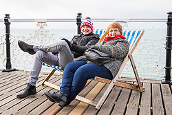 © Licensed to London News Pictures. 03/12/2017. Brighton, UK. BEVERLY SMITH and ANDREW ADAMS from Kent spending time on the Brighton Palace dressed up in hats and scarfs as cold weather is hitting the seaside resort. Photo credit: Hugo Michiels/LNP