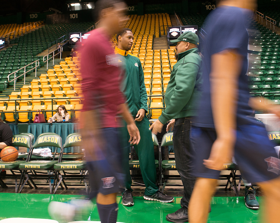 December 5, 2015 - Fairfax, VA - A day in the life of &quot;Doc Nix,&quot; aka Dr. Michael Nickens, the Director of the Athletic Bands for George Mason University. Here, Doc Nix talks with one of the basketball players before the game.<br /> <br /> <br /> Photo by Susana Raab