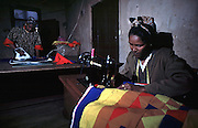 Misir, 26, (left) and Zunesh, 28, working in fear of being discovered by their neighbours that they are both HIV positive. If so, they would be forced out of the single room where they make a modest living sewing colourful blankets and pillow covers.<br />Picture Credit: Dermot Tatlow