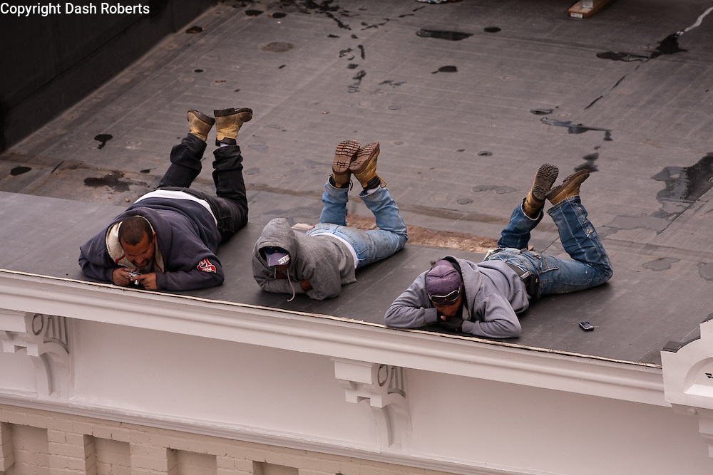 Construction workers lay on ledge of building to view 2009 Veteran's Day Parade in downtown Knoxville.