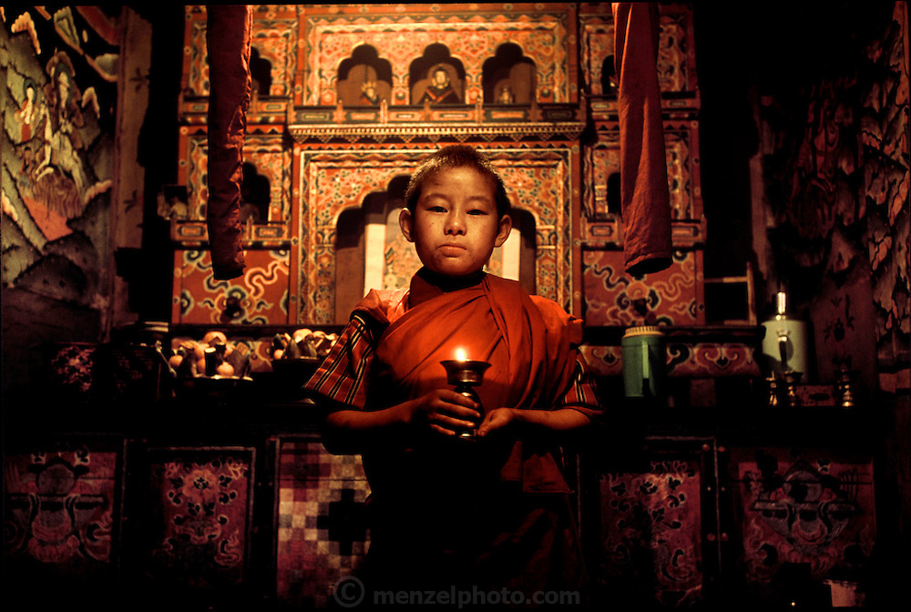 (MODEL RELEASED IMAGE). Chato Namgay in Shingkhey, Bhutan standing with a lamp inside the prayer room of his family's house. (Supporting image from the project Hungry Planet: What the World Eats.) The Namgay family living in the remote mountain village of Shingkhey, Bhutan, is one of the thirty families featured, with a weeks' worth of food, in the book Hungry Planet: What the World Eats.