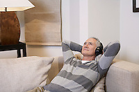 Middle-aged man listentening to music on headphones in living room