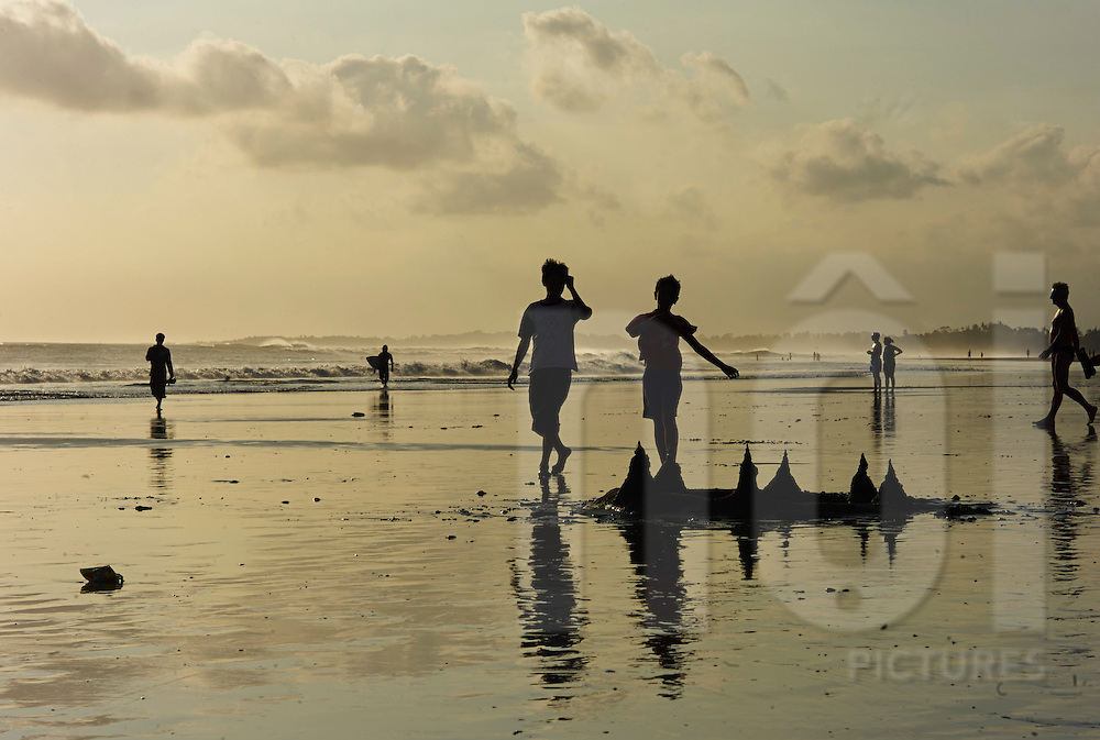 Silhouetted beach-goers on Kuta Beach at sunset in Bali, Indonesia, Southeast Asia