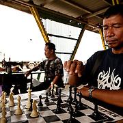 Men play chess at a market in Kota Kinabalu, Sabah, Malaysia.
