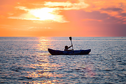 © Licenced to London News Pictures. Aberystwyth Wales UK, Thursday 26 July 2018. UK Weather: A lone kayaker is  silhouetted by the setting sun over the sea in Aberystwyth at the end of a day of record breaking hot summer sunshine.  The UK wide heatwave continues, with little real respite from the very dry weather  despite some rain in the forecast for the weekend. Photo credit: Keith Morris/LNP