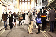 People drinking outside a bar in Soho, London, in winter