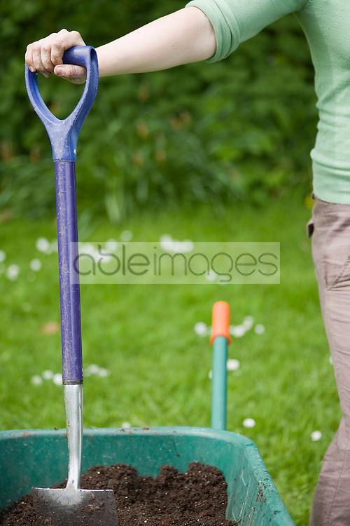 Young woman standing next to wheelbarrow with garden spade