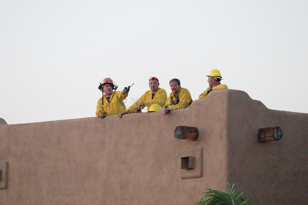 Firefighters watch a wildfire from atop a house in Desert Hills,AZ