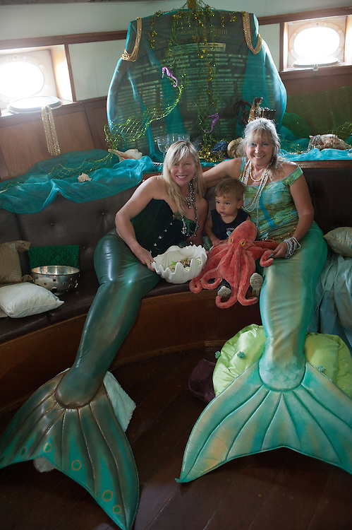 little boy looking dumb founded, surrounde by two women, costumed as mermaids, and red plush octopus