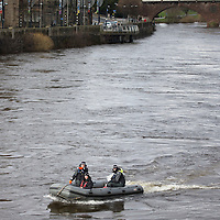 Officers from a Police Scotland underwater search team pictured on the River Tay Street in Perth where they today continued the search for a body after an off duty firefighter reported spotting a body in the river last night (Sunday 23.02.14). The search was halted at 9.30pm Sunday evening....24.02.14<br /> Picture by Graeme Hart.<br /> Copyright Perthshire Picture Agency<br /> Tel: 01738 623350  Mobile: 07990 594431