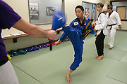 Isaiah Gonsalves kicks a target during a family class at Master Kim's Tae Kwon Do in Penfield on Thursday, August 20, 2015.