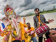 "15 SEPTEMBER 2013 - BANGKOK, THAILAND: Hindus in Bangkok sing and praise Ganesha before pushing the statues of Ganesha into the Chao Phraya River on the last day of Ganesha Chaturthi celebrations at Shiva Temple in Bangkok. Ganesha Chaturthi is the Hindu festival celebrated on the day of the re-birth of Lord Ganesha, the son of Shiva and Parvati. The festival, also known as Ganeshotsav (""Festival of Ganesha"") is observed in the Hindu calendar month of Bhaadrapada. The festival lasts for 10 days, ending on Anant Chaturdashi. Ganesha is a widely worshipped Hindu deity and is revered by many Thai Buddhists. Ganesha is widely revered as the remover of obstacles, the patron of arts and sciences and the deva of intellect and wisdom. The last day of the festival is marked by the immersion of the deity, which symbolizes the cycle of creation and dissolution in nature.  In Bangkok, the deity (statue) was submerged in the Chao Phraya River.         PHOTO BY JACK KURTZ"